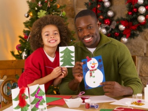 African American father and mixed race son making Christmas cards